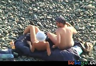 Voyeur on public beach. Oral lovemaking